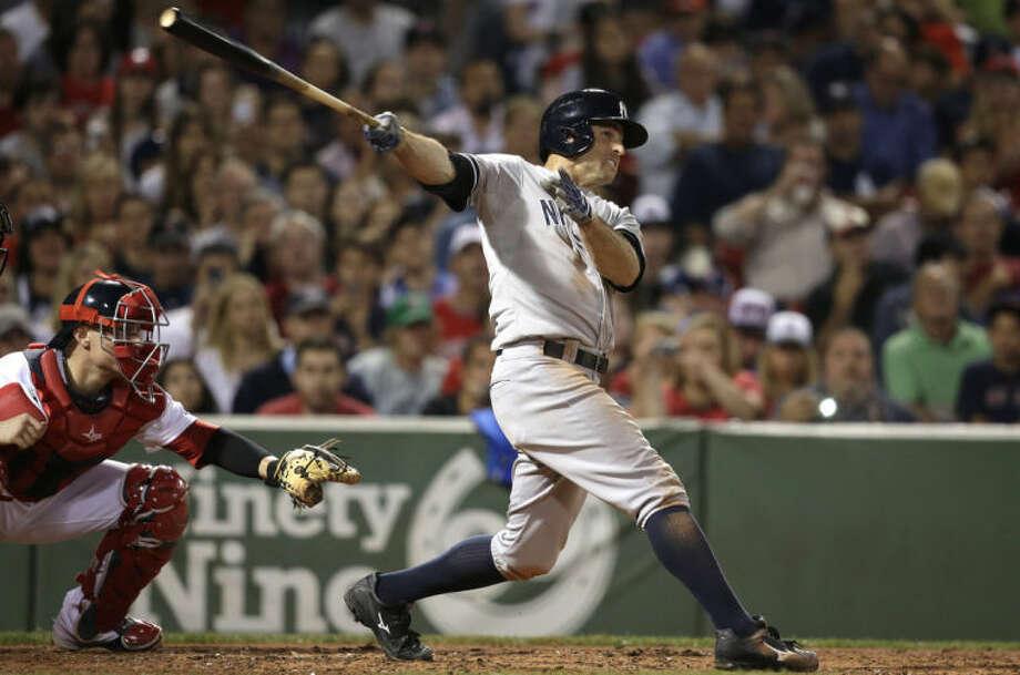 New York Yankees' Brett Gardner, right, hits a two-run double as Boston Red Sox catcher Christian Vazquez, left, looks on in the second inning of a baseball game, in Boston, Sunday, Aug. 3, 2014. (AP Photo/Steven Senne)