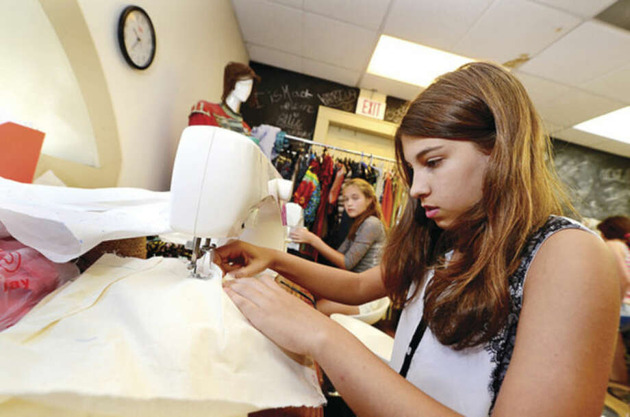 Left, 12-year-old Ava Aguiar uses a sewing machine to put together her clothing design during the camp this week. Right, New England Fashion and Design Association president Irina Simeonova, center, helps her summer campers, including Katie Rowe and Sofia Nazer, this week at their facility at the South Norwalk train station.