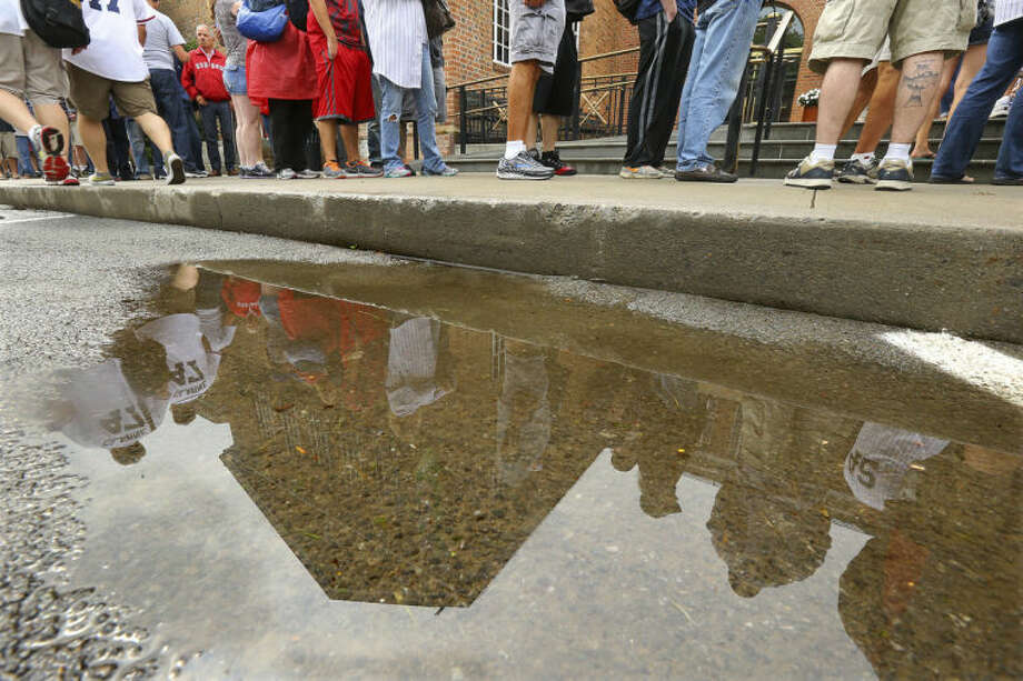 Hundreds of baseball fans are reflected in a puddle of rain water along with the building as they line up outside the National Baseball Hall of Fame despite the weather on Sunday, July 27, 2014, in Cooperstown. The annual Hall of Fame Induction Ceremony will take place nearby at the Clarks Sports Center. (AP Photo/Atlanta Journal-Constitution, Curtis Compton) MARIETTA DAILY OUT; GWINNETT DAILY POST OUT; LOCAL TELEVISION OUT; WXIA-TV OUT; WGCL-TV OUT