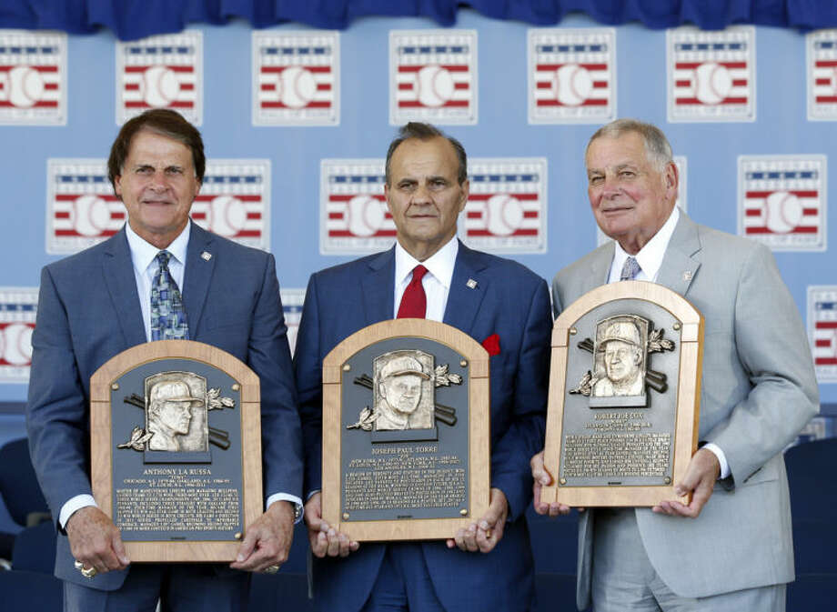 National Baseball Hall of Fame inductees, from left to right, Tony La Russa, Joe Torre and Bobby Cox hold their plaques after an induction ceremony at the Clark Sports Center on Sunday, July 27, 2014, in Cooperstown, N.Y. (AP Photo/Mike Groll)