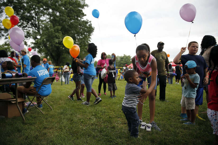 "In this July 25, 2015, photo, children hold balloons at a community gathering in Ferguson, Mo. Dubbed a ""Day of Hope"" more than 40 area churches along with help from Convoy of Hope organized the event to bring people in the community together for a ""stress free"" day. (AP Photo/Jeff Roberson)"