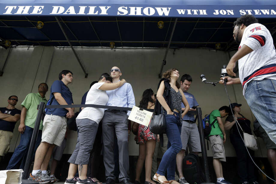 "Alexandra Mele, second from right, is interviewed and Ariana and Isaac Levin, embrace as they wait in line to enter for the final taping of ""The Daily Show with Jon Stewart,"" Thursday, Aug. 6, 2015, in New York. Stewart says goodbye on Thursday, after 16 years on the show that established him as America's foremost satirist of politicians and the media. (AP Photo/Mary Altaffer)"