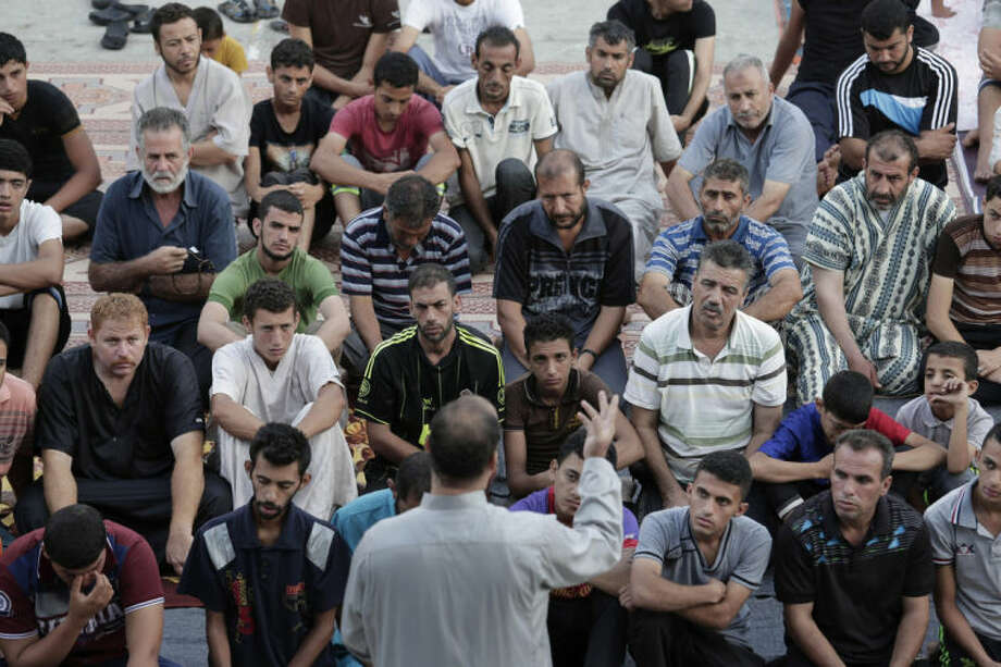 Palestinians listen to a sermon as they pray in the courtyard of a U.N. school in Gaza City, Monday, July 28, 2014. The school, one of dozens of emergency shelters for those who have fled the fighting. It's the morning of Eid al-Fitr, the three-day holiday that caps the Muslim fasting month of Ramadan. In normal times, the men would have worshipped at their neighborhood mosques. However, 20 mosques have been hit by Israeli warplanes so far, according to Palestinian officials. Israel says Hamas stores weapons and rockets in houses of worship. The men prefer to perform Eid prayers in the relative safety of the school. (AP Photo/Lefteris Pitarakis)