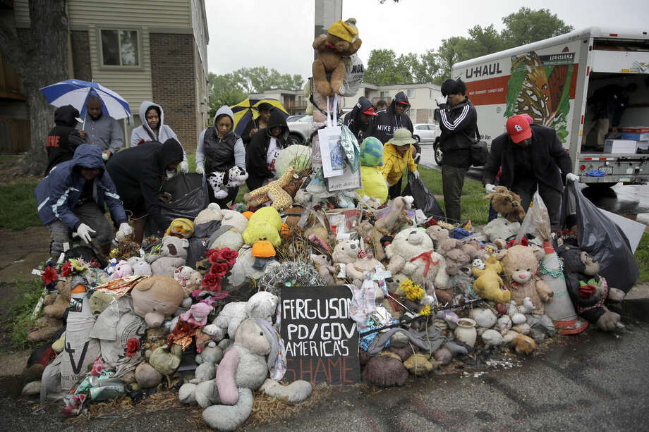 FILE- In this May 20, 2015 file photo, volunteers remove items left at a makeshift memorial for Michael Brown on what would have been Brown's 19th birthday in Ferguson, Mo. Family and community members cleared out a collection of stuffed animals, candles and other trinkets that for months served as a shrine in the middle of Canfield Drive, the site of the shooting. A permanent plaque in his memory and marker at the site of the shooting were installed nearby. (AP Photo/Jeff Roberson, File)
