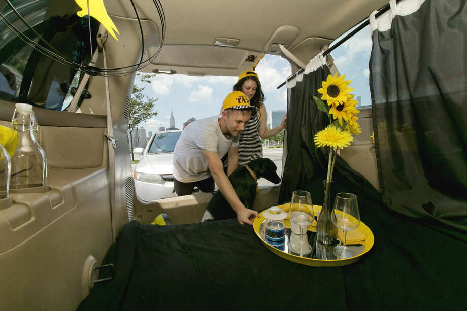 In this Monday, Aug. 3, 2015, photo, Airbnb renters Michael and Tabitha Akins, and their dog Bagheera, check their accommodations in a decommissioned 2002 Honda Odyssey yellow taxi, in the Queens borough of New York. Their view includes the Empire State Building, background left. (AP Photo/Richard Drew)