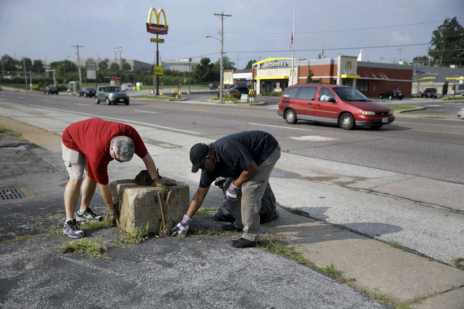 In this July 27, 2015, photo, Tim Fitch, left, and Rodney Crim pull weeds and pick up trash as they join a group of volunteers working to clean up a section of West Florissant Avenue in Ferguson, Mo. West Florissant, the site of much of the unrest after the shooting of Michael Brown, is poised to get $37 million in upgrades. The improvement plan is expected to include bricked sidewalks, bicycle lanes, stylish lampposts and landscaping. (AP Photo/Jeff Roberson)