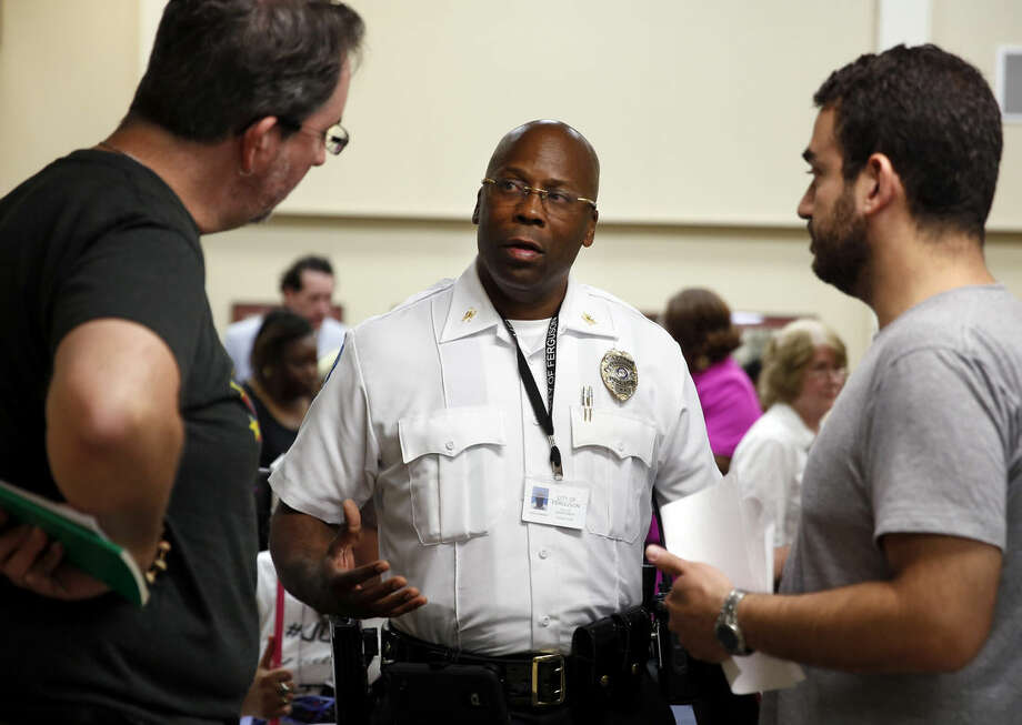 In this July 28, 2015, photo, interim police chief Andre Anderson, center, talks with activists John Powell, left, and Marc DeSantis at the end of a city council meeting in Ferguson, Mo. Anderson says he wants his officers engaging with the community, getting out of their cars and mingling with people in an effort to build better relations. (AP Photo/Jeff Roberson)