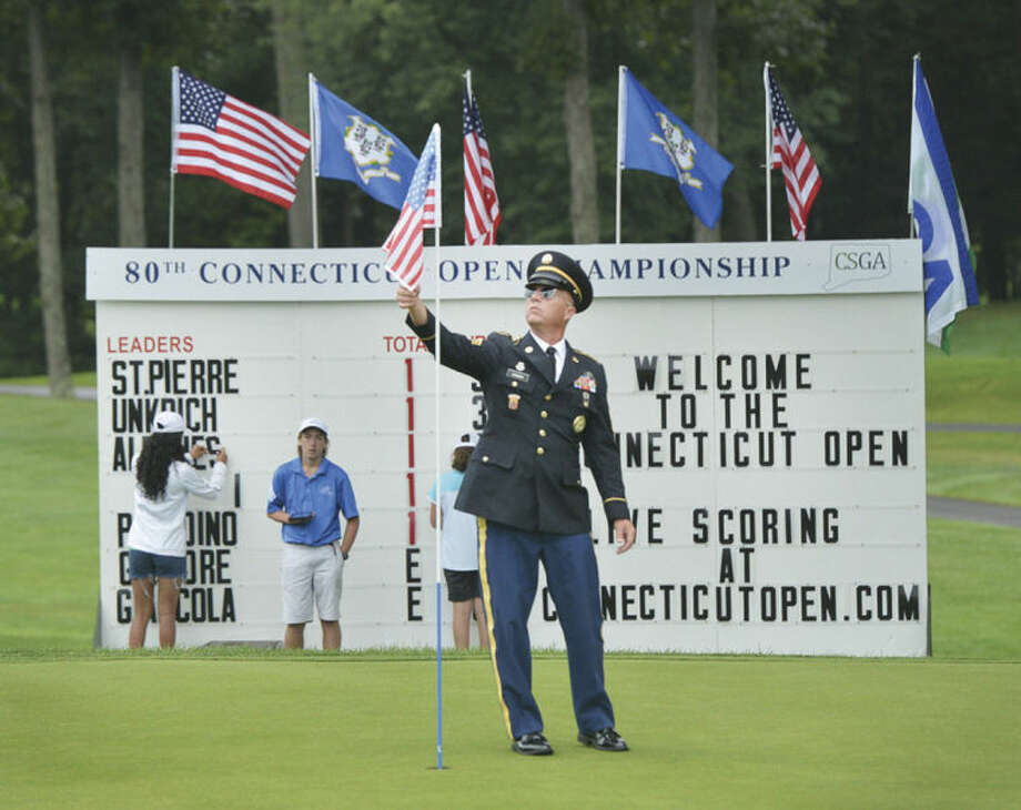 Hour photo/Alex von KleydorffSgt. First Class Mark Spencer straightens the American flag on the 18th green at the 80th Connecticut Open Championship at Rolling Hills Country Club Monday.