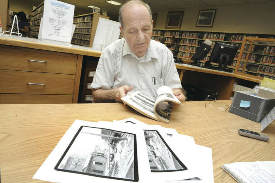 Hour photos/Matthew VinciRalph Bloom, Norwalk historian and volunteer at the Norwalk Public Library, peruses photos at the library's history room as he researches information on bridge construction in Norwalk during the 1890s.