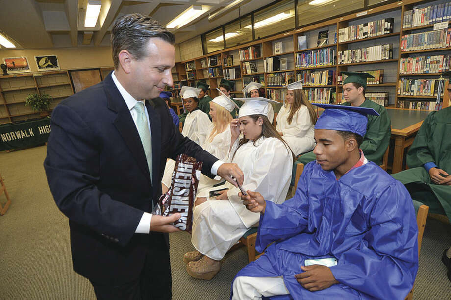 Hour Photo/Alex von Kleydorff Sen. Bob Duff hands out chocolate bars after telling the graduates about Milton Hershey who was a dropout during the class of 2015 Summer Graduation