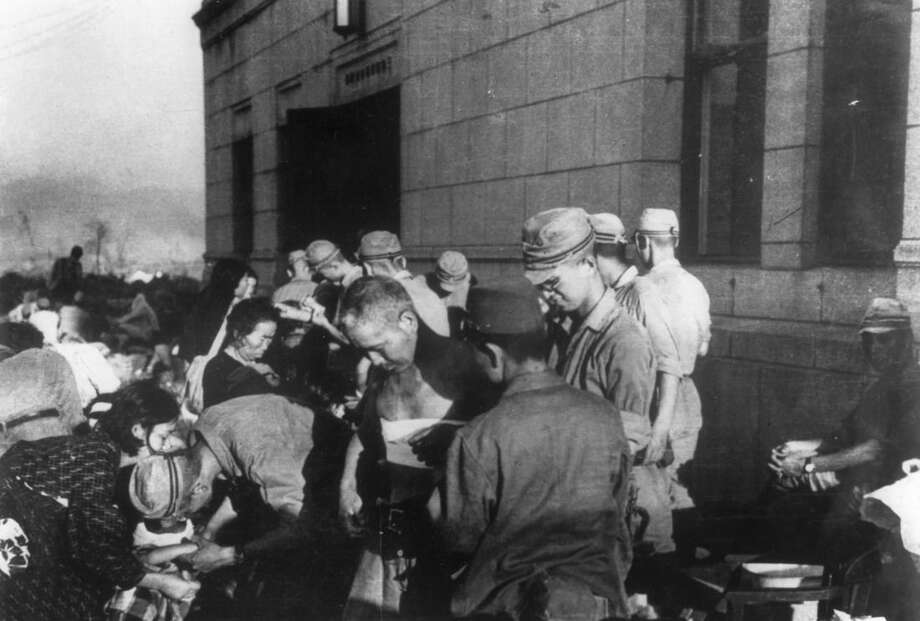 FILE- In this Aug. 6, 1945, file photo, shortly after the first atomic bomb ever used in warfare was dropped by the United States over the Japanese city of Hiroshima, survivors are seen as they receive emergency treatment by military medics. (AP Photo, File)