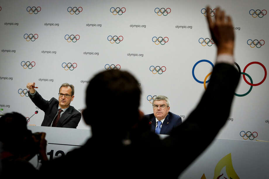 International Olympic Committee President Thomas Bach, right, accompanied by IOC Director of Communications Mark Adams, takes a question during a press conference after the 128th IOC session in Kuala Lumpur, Malaysia Monday, Aug. 3, 2015. Bach says the Olympic body will take action against any Olympic medalists if they are found guilty of the latest doping allegations in track and field. (AP Photo/Joshua Paul)