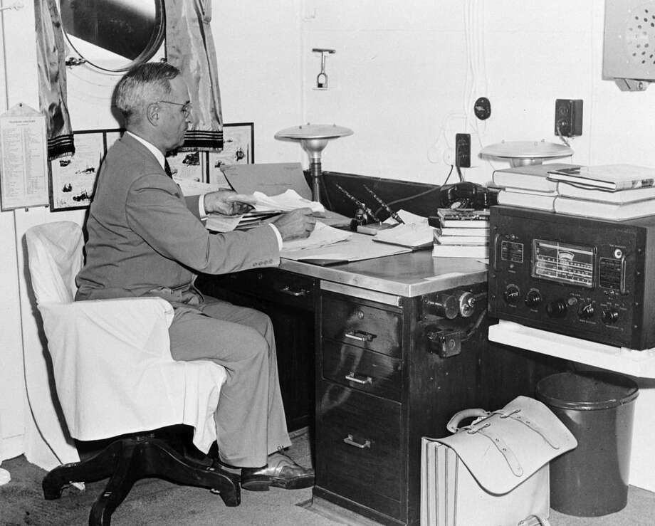 FILE- In this Aug. 6, 1945, file photo, aboard the cruiser Augusta, President Harry S. Truman, with a radio at hand, reads reports of the first atomic bomb raid on Japan, while en route home from the Potsdam conference. On two days in August 1945, U.S. planes dropped two atomic bombs, one on Hiroshima, one on Nagasaki, the first and only time nuclear weapons have been used. Their destructive power was unprecedented, incinerating buildings and people, and leaving lifelong scars on survivors, not just physical but also psychological, and on the cities themselves. Days later, World War II was over. (AP Photo, File)