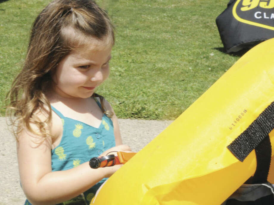 Shia Borelli, 3, gets her first look at a flotation device during the water safety day at Calf Pasture Beach in Norwalk Sunday.
