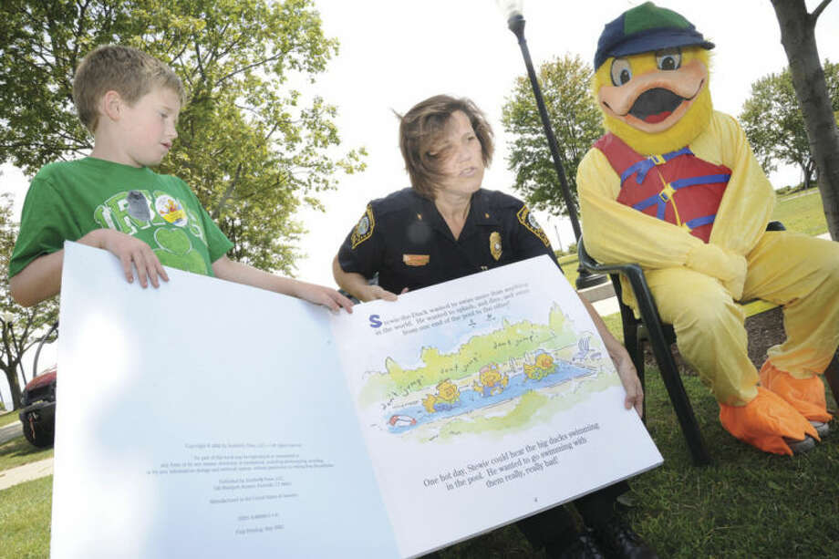 """Hour photos/Matthew VinciNorwalk Police deputy chief Susan Zecca, with the help of Ryan Blake, 8, reads the """"Stewie the Duck"""" book to children at Calf Pasture Beach in Norwalk Sunday for the water safety day presented by the Stuart Leonard Jr. Foundation, the Norwalk Police Department and the Norwalk Department of Recreation and Parks."""
