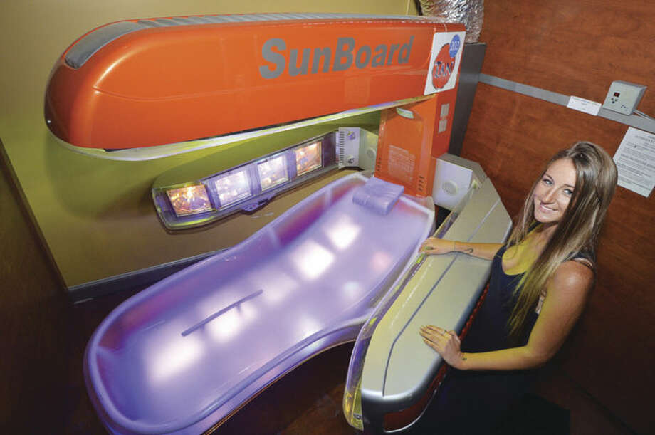 Hour Photo/Alex von Kleydorff203 Tan Co.'s Brittany Lyons with their Platinum Level SunBoard tanning bed which uses only UVA rays