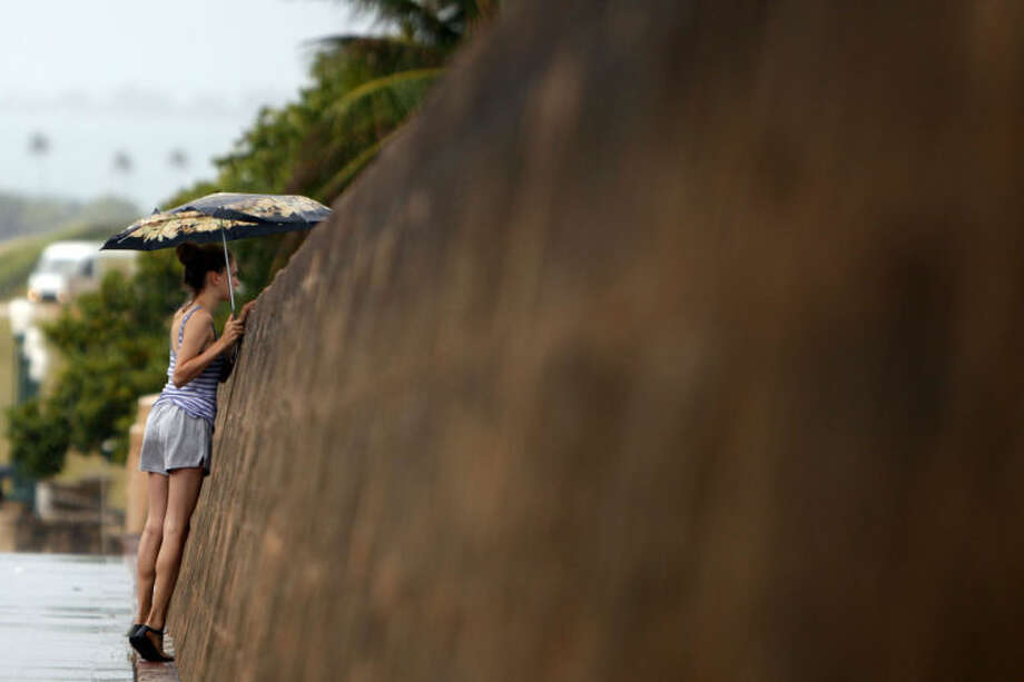 A woman looks over the seaside wall of the 16th century Spanish fort El Morro, under cloudy skies in San Juan, Puerto Rico, Saturday, Aug. 2, 2014. Bertha pushed just south of Puerto Rico on Saturday as it unleashed heavy rains and strong winds across the region. (AP Photo/Ricardo Arduengo)