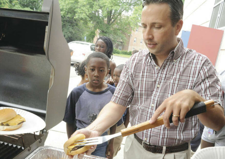 Hour photo/Matthew VinciState Sen. Bob Duff volunteers Saturday at the grill with 8-year-old Omega Smith at the Ely School for the Roodner Court Family fun Day.