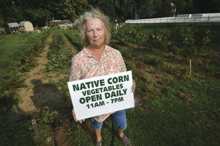 Hour Photo/Alex von Kleydorff In the garden at Bucciarelli Farm, Donna Benz holds one of the signs she had made to help people find her neigborhood farm stand.