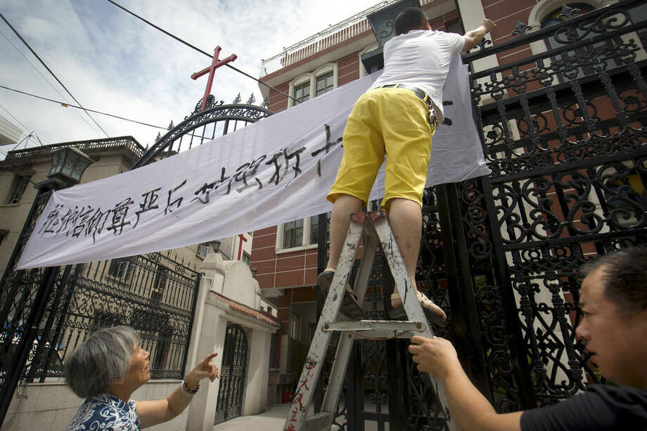 """In this July 30, 2015 photo, church members put up a banner reading """"Safeguard the dignity of belief, oppose the forcible removal of crosses"""" at the entrance of the Jingda Catholic Church in Jingda Village in Yongjia County in eastern China's Zhejiang Province. A massive government campaign is underway in Zhejiang, where authorities are believed to be under a two-month deadline to remove crosses from the spires, vaults, roofs and wall arches of the 4,000 or so Protestant and Catholic churches that dot the landscape of the region. (AP Photo/Mark Schiefelbein)"""
