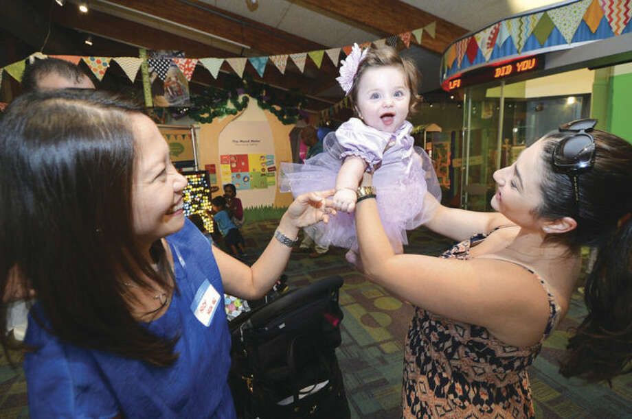 Hour Photo/Alex von Kleydorff Norwalk Hospital NICU Nurse Nicy Tomo says hi and gets a big smile from former patient 7.5 month old Sophia Papadopoulos and mom and dad Zoe and Nick, during a celebration reunion at Stepping Stones Museum for Children