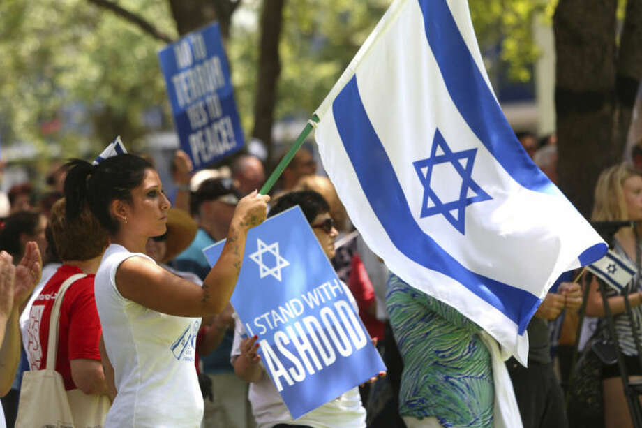 Nofar Haymovich of Israel who is currently staying in Lakeland displays the Israeli flag during a rally held in Lykes Gaslight Square Park in downtown Tampa on Friday Aug. 1, 2014. Hundreds of people from across Tampa Bay joined together in the park at noon as a sign of solidarity in support of Israel and Ashdod (TampaÍs Sister City) during this time of unrest and continually rising conflict between Israel and Hamas in the Gaza Strip. (AP Photo/The Tampa Bay Times, Skip O'Rourke)
