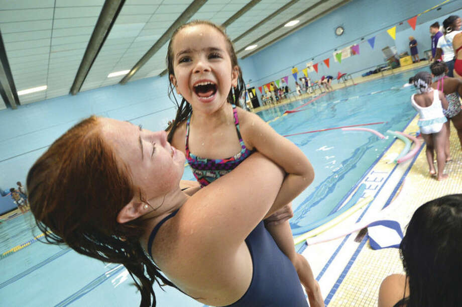 Hour Photo/Alex von Kleydorff Swim Safety Instructor and Lifeguard Becca Riina helps 5yr old Daniella Garcia from the pool after a group from the Carver Center learned about water safety from The Wilton family Y