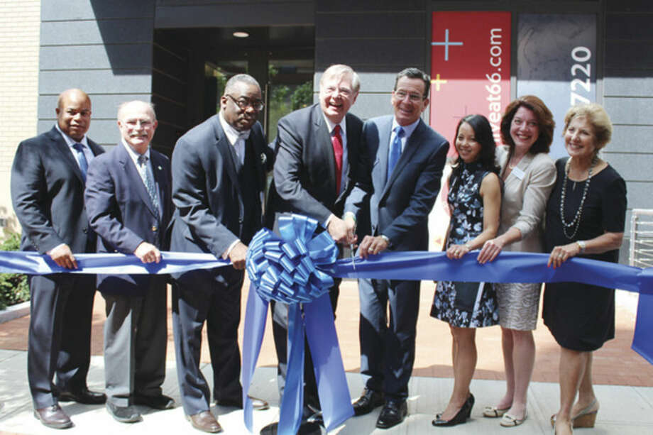 Times photo/Miranda ZhangStamford Mayor David Martin and Governor Dannel Malloy (center) ceremoneously cut the ribbon at the grand opening of a new downtown apartment complex onSummer Street.