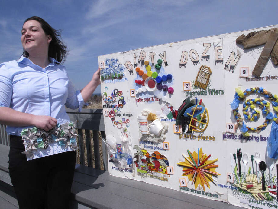 FILE - In this April 13, 2015, file photo, Erin O'Neill, a student volunteer with the Clean Ocean Action environmental group, holds a poster in Sandy Hook, N.J. showing some of the items of trash that volunteers removed from New Jersey's beaches the previous spring and fall. For years along the Cornish coast of Britain, Atlantic Ocean currents have carried thousands of Lego pieces onto the beaches. In Kenya, cheap flip-flop sandals are churned relentlessly in the Indian Ocean surf, until finally being spit out onto the sand. In Bangladesh, fishermen are haunted by floating corpses that the Bay of Bengal sometimes puts in their path. And now, perhaps, the oceans have revealed something else: parts of Malaysian Airlines Flight 370, the jetliner that vanished 17 months ago with 239 people on board. (AP Photo/Wayne Parry, File)