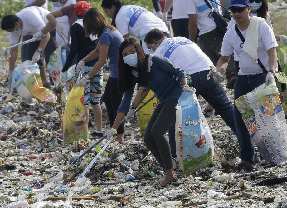 """FILE - In this June 8, 2013 file photo, volunteers and environmentalists remove dirt and garbage that were washed ashore at a bird sanctuary, known as """"Freedom Island,"""" during a World Ocean Day event at Paranaque, south of Manila, Philippines. For years along the Cornish coast of Britain, Atlantic Ocean currents have carried thousands of Lego pieces onto the beaches. In Kenya, cheap flip-flop sandals are churned relentlessly in the Indian Ocean surf, until finally being spit out onto the sand. In Bangladesh, fishermen are haunted by floating corpses that the Bay of Bengal sometimes puts in their path. And now, perhaps, the oceans have revealed something else: parts of Malaysian Airlines Flight 370, the jetliner that vanished 17 months ago with 239 people on board. (AP Photo/Bullit Marquez, File)"""