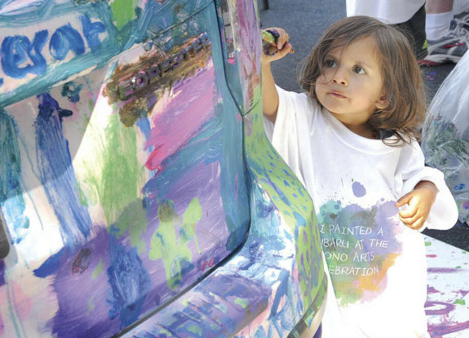 Hour photo/Matthew VinciCariad Samy, 2, paints a donated car from Garavel Auto Group Sunday at the 40th annual SoNo Arts Celebration.