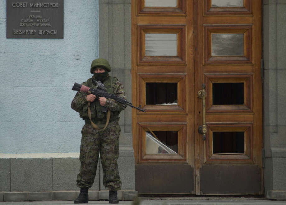 An unidentified man guards the entrance to a local government building in Simferopol, Ukraine, on Saturday, March 1, 2014. Russian President Vladimir Putin asked parliament Saturday for permission to use the country's military in Ukraine, moving to formalize what Ukrainian officials described as an ongoing deployment of Russian military on the country's strategic region of Crimea. (AP Photo/Ivan Sekretarev)