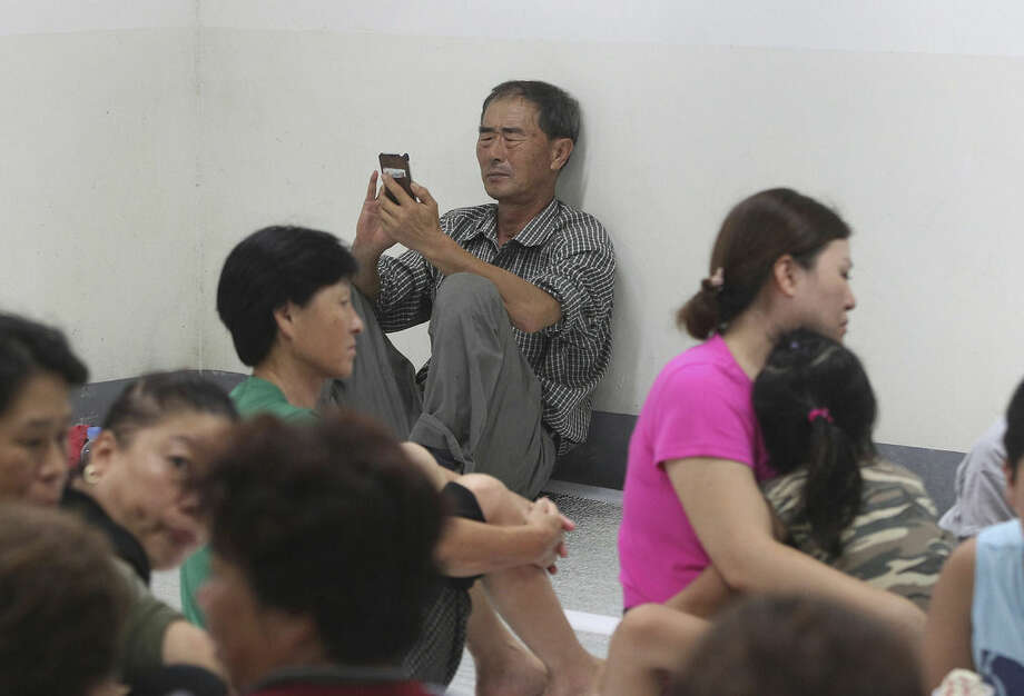 A South Korean resident watches his mobile phone to read news as people gather at a shelter in the South Korean town of Yeoncheon where the shell fell Thursday, Aug. 20, 2015. South Korea's military fired dozens of shells Thursday at rival North Korea after the North lobbed a single artillery round at the border town, the South's Defense ministry said. (AP Photo/Ahn Young-joon)