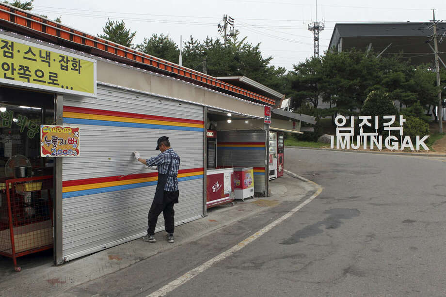 A man locks a shutter of his shop after an evacuation order is issued to the residents and visitors at the Imjingak Pavilion near the border village of Panmunjom, which has separated the two Koreas since the Korean War, in Paju, north of Seoul, South Korea, Thursday, Aug. 20, 2015. South Korea's military fired dozens of shells Thursday at rival North Korea after the North lobbed a single artillery round at a South Korean border town, the South's Defense ministry said. (Kim Seung-doo/Yonhap via AP) KOREA OUT
