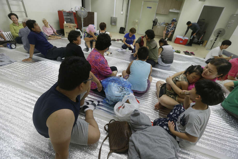 South Korean residents gather at a shelter in the South Korean town of Yeoncheon where the shell fell Thursday, Aug. 20, 2015. South Korea's military fired dozens of shells Thursday at rival North Korea after the North lobbed a single artillery round at the border town, the South's Defense ministry said. (AP Photo/Ahn Young-joon)