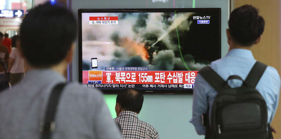 """People watch a television news program reporting about South Korea's respond to the North with a file video footage at Seoul train station in Seoul, South Korea, Thursday, Aug. 20, 2015. South Korea's military fired dozens of shells Thursday at rival North Korea after the North lobbed a single artillery round at a South Korean border town, the South's Defense ministry said. The letters read """"South Korean military, respond 155mm shells to the North."""" (Kim Do-hun/Yonhap via AP) KOREA OUT"""