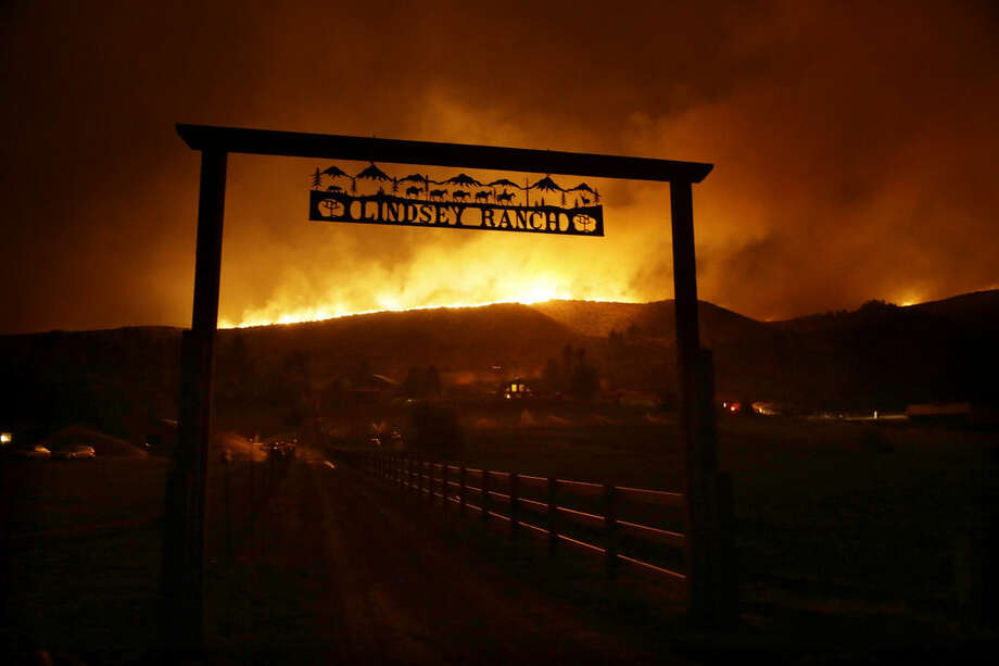 Fire burns on the ridge above a ranch on Twisp River Road in Twisp, Wash., Wednesday, Aug. 19, 2015. Authorities on Wednesday afternoon urged people in the north-central Washington town to evacuate because of a fast-moving wildfire. (AP Photo/Ted S. Warren)