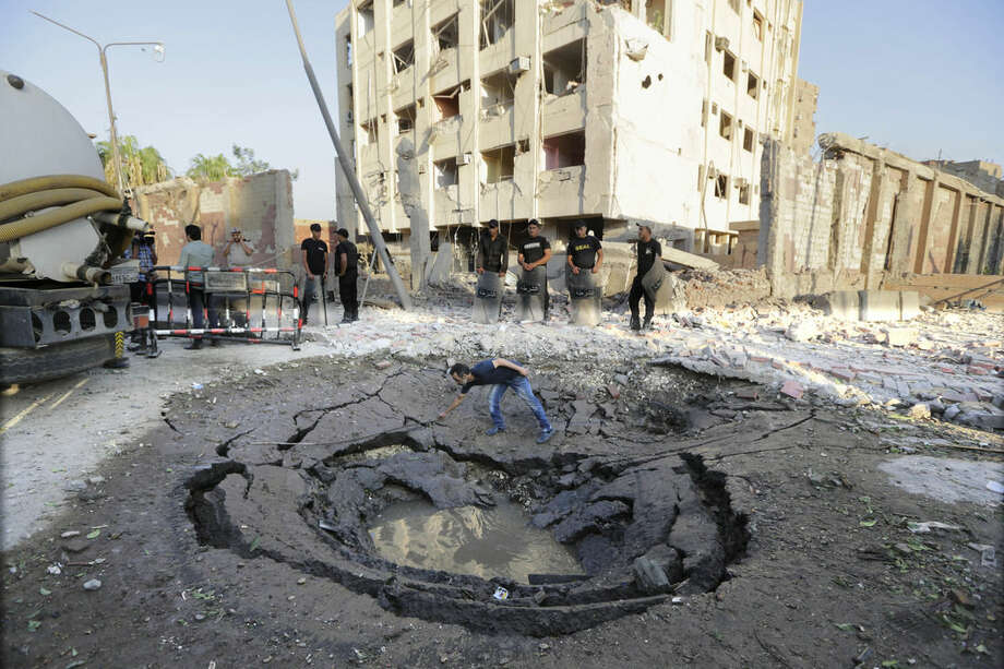 An Egyptian worker checks a hole believed to be caused by the bombing in the street outside the national security building early Thursday, Aug. 20, 2015, in the Shubra el-Kheima neighborhood of Cairo. A massive car bomb exploded early Thursday in a popular residential neighborhood in Cairo, blowing the facades off nearby buildings, Egyptian security officials said. (AP Photo/Amr Nabil)