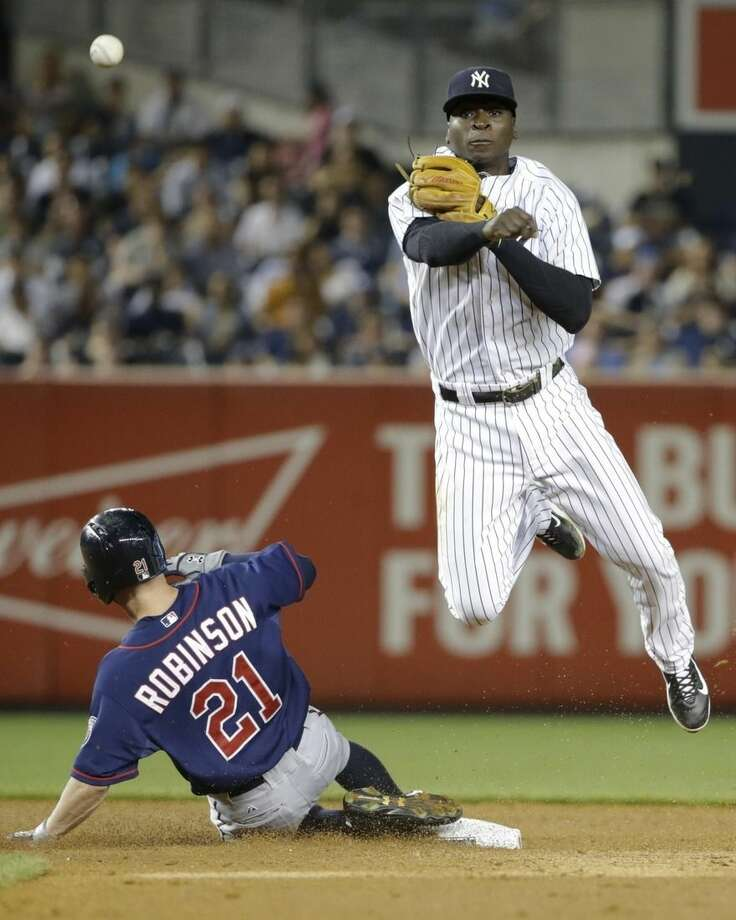 New York Yankees shortstop Didi Gregorius, right, throws out Minnesota Twins' Aaron Hicks at first base after forcing out Shane Robinson (21) on a double play during the sixth inning of a baseball game Tuesday, Aug. 18, 2015, in New York. (AP Photo/Frank Franklin II)