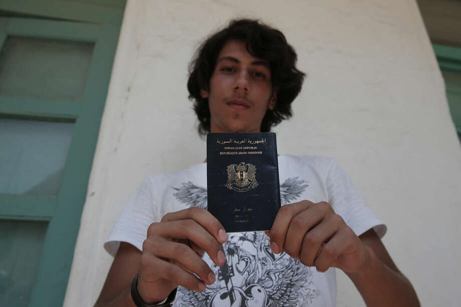 Syrian refugee Mouradin, 16, last name not given, holds his Syrian passport, as he waits to be registered outside the local coast guard building in the Greek island of Leros, Monday, Aug. 17, 2015. This Greek island that was once a place of exile for political prisoners has become one of the country's most welcoming communities for migrants fleeing chaos and war, thanks to a dedicated grass-roots volunteer network and tourists interrupting their vacations to provide what help they can. But even on Leros, a 75-square kilometer (29 sq. mile) rocky outcrop in the Aegean Sea with a permanent population of fewer than 10,000 people, the welcome mat is fraying under the sheer numbers of migrants _ hundreds arrive in smugglers' boats most days _ making the perilous boat journey here across the Aegean Sea from Turkey. (AP Photo/Lefteris Pitarakis)