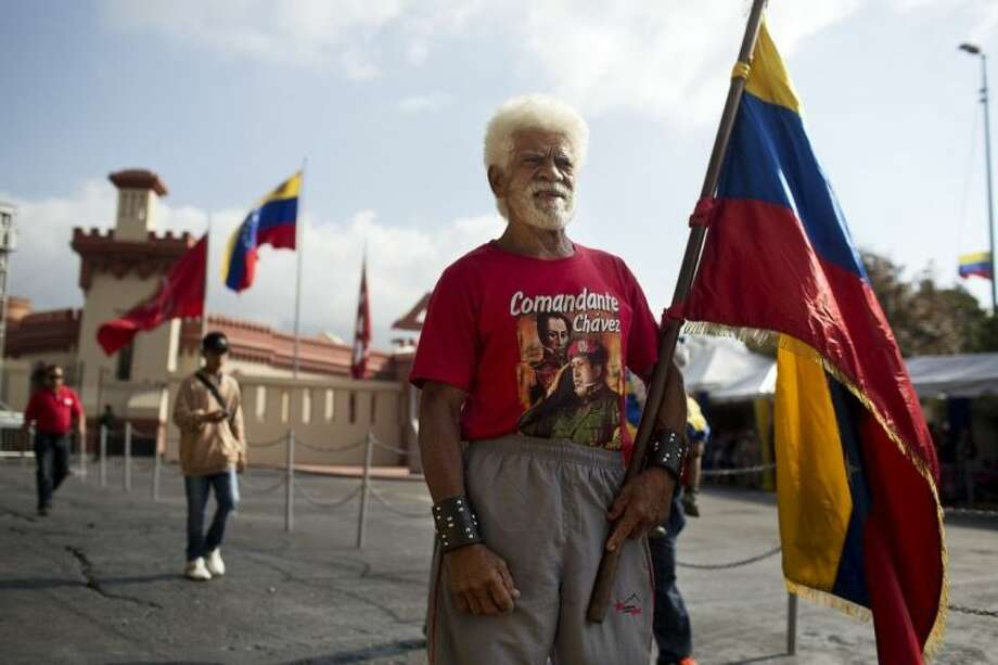 """Pablo de la Cruz Aldana poses for a photo after visiting the mausoleum of the late Venezuelan President Hugo Chavez in Caracas, Venezuela, Wednesday, March 5, 2014. He's been dead a year, but Chavez's face and voice are everywhere. President Nicolas Maduro announced 10 days of commemoration beginning Wednesday morning with a military parade in Caracas followed by a remembrance ceremony at Chavez's mausoleum and capped with the debut of director Oliver Stone's documentary """"My Friend Hugo."""" (AP Photo/Rodrigo Abd)"""