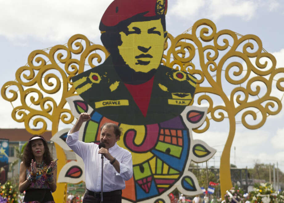 Nicaragua's President Daniel Ortega, accompanied by his wife, first lady Rosario Murillo, talks during an event to mark the first anniversary of the death of Venezuela's late president Hugo Chavez, in Managua, Nicaragua, Wednesday, March 5, 2014. (AP Photo/Esteban Felix)
