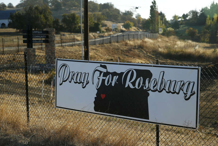 A sign hangs on a fence near the road leading to the Umpqua Community College campus Friday, Oct. 2, 2015, in Roseburg, Ore. Armed with multiple guns, Chris Harper Mercer, 26, walked into a classroom at the community college, Thursday, and opened fire, killing multiple people and wounding several others. (AP Photo/John Locher)
