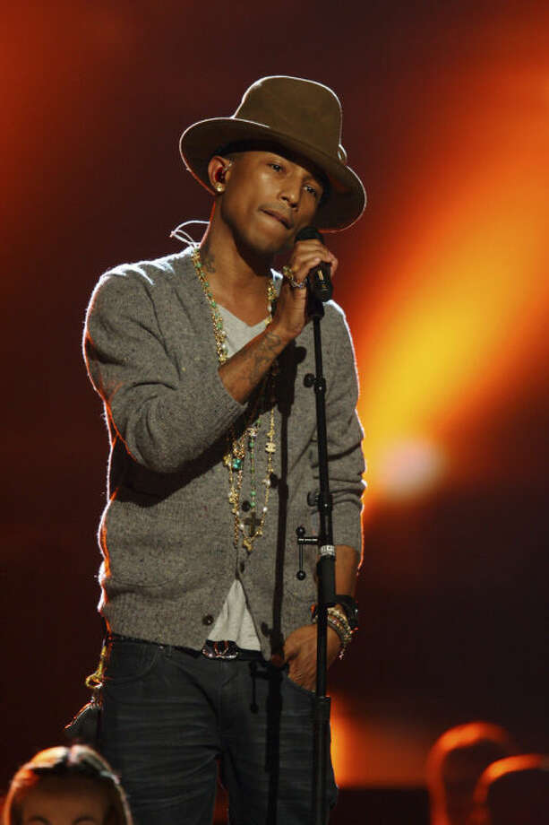 "FILE - This Jan. 27, 2014 file photo shows Pharrell Williams performing at The Night that Changed America: A Grammy Salute to the Beatles in Los Angeles. This week Pharrell released his sophomore solo album, ""G I R L,"" which features the Oscar-nominated hit, ""Happy."" The song is spending its second week on top of the Billboard Hot 100 chart. (Photo by Zach Cordner/Invision/AP, File)"