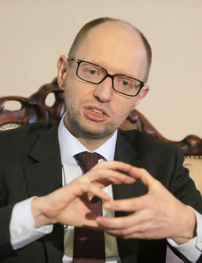 Ukrainian Prime Minister Arseniy Yatsenyuk talks with reporters during an interview with the Associated Press in Kiev, Ukraine, Wednesday March 5, 2014. Yatsenyuk said Wednesday that embattled Crimea must remain part of Ukraine, but may be granted more local powers. (AP Photo/Efrem Lukatsky)
