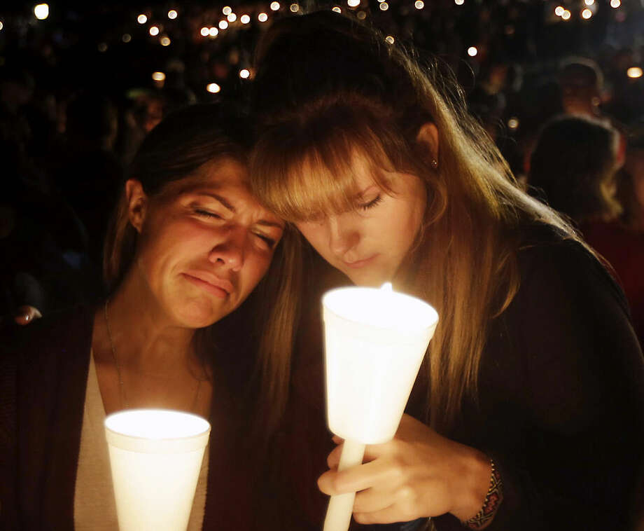 Kristen Sterner, left, and Carrissa Welding, both students of Umpqua Community College, embrace each other during a candle light vigil for those killed during a shooting at the college, Thursday, Oct. 1, 2015, in Roseburg, Ore. (AP Photo/Rich Pedroncelli)