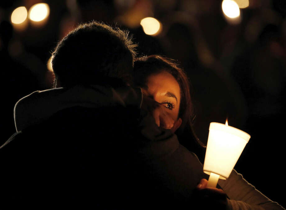 Umpqua Community College student Nichole Zamarripa, right, is consoled during a candlelight vigil for those killed during a shooting at the school, Thursday, Oct. 1, 2015, in Roseburg, Ore. (AP Photo/Rich Pedroncelli)