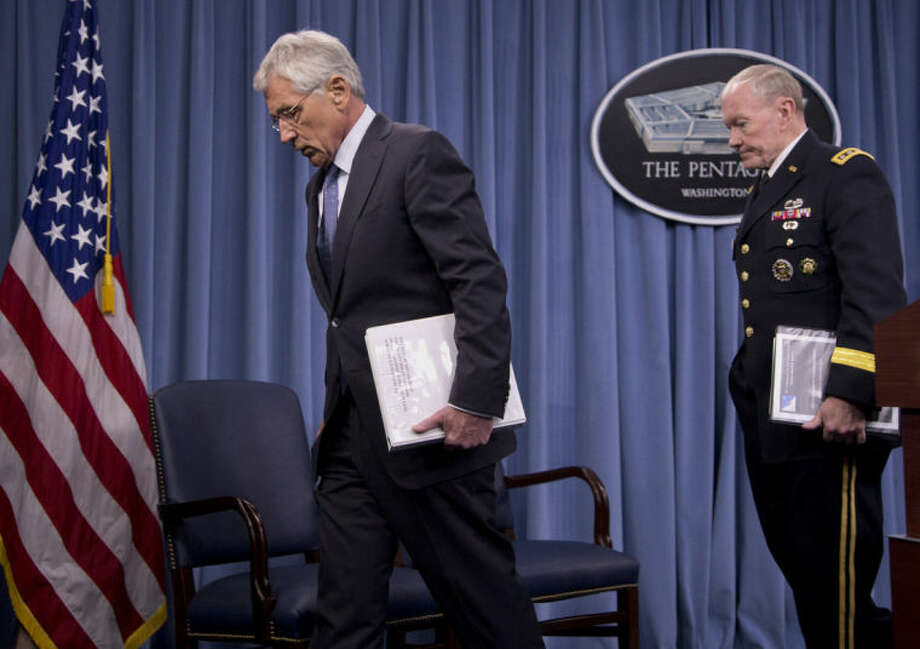 Joint Chiefs Chairman Gen. Martin Dempsey follows Defense Secretary Chuck Hagel after a news conference at the Pentagon, Monday, Feb. 24, 2014, where Hagel recommended shrinking the Army to its smallest size since the buildup to U.S. involvement in World War II in an effort to balance postwar defense needs with budget realities. (AP Photo/Carolyn Kaster)