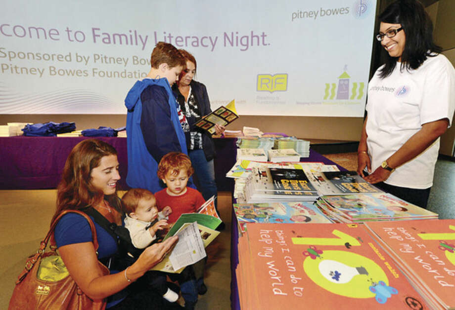 "Hour photo / Erik Trautmann Pitney Bowes volunteer Vina Goberdhen, right, helps Kristen Good and her children, Melissa and Jackson find books during the ""Family Literacy Night"" at Stepping Stones Museum for Children Thursday presented by Reading is Fundamental (RIF) and the Pitney Bowes Foundation."