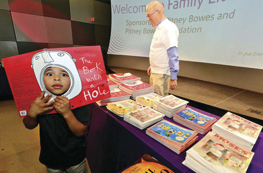 "Hour photo / Erik Trautmann 5 year old Jackson Plummer picks out a book during ""Family Literacy Night"" at Stepping Stones Museum for Children Thursday presented by Reading is Fundamental (RIF) and the Pitney Bowes Foundation."